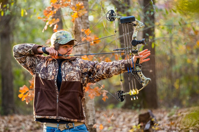 Bow shooting a compound bow in woods
