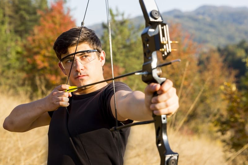Man aiming compound bow