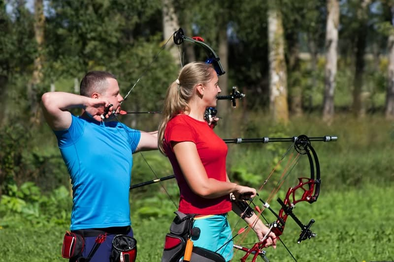 Man and Woman Shooting Compound Bows