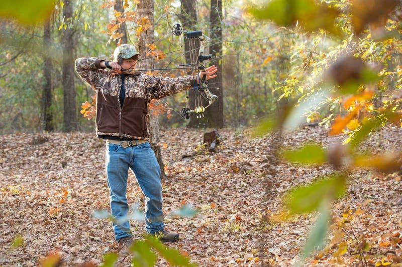 Boy Shooting Compound Bow In Woods